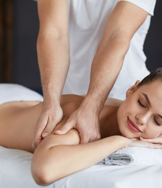Young beautiful woman enjoying back and shouders massage in spa.Professional massage therapist is treating a female patient in apartment.Relaxation, beauty, body and face treatment concept.Home massage.
